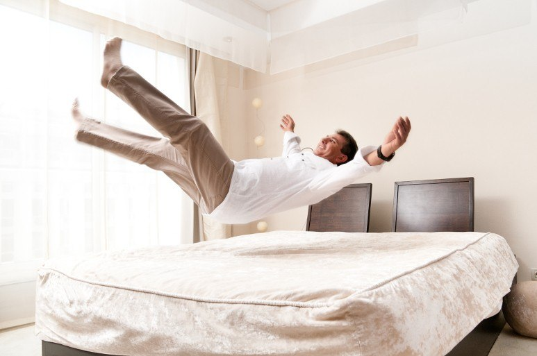 Man happily jumping on sofa bed mattress