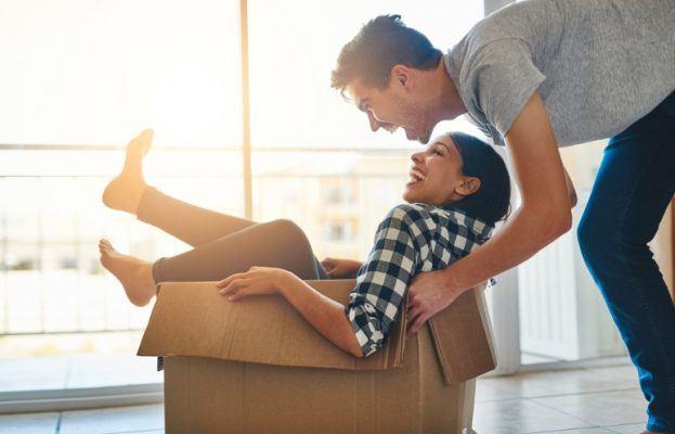 Couple having fun while packing away their RV mattress