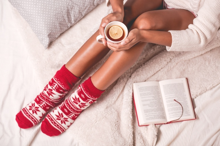 Woman ins bed with winter socks and a hot cup of tea
