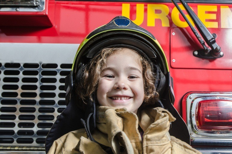 Kid in a firefighter coat and helmet