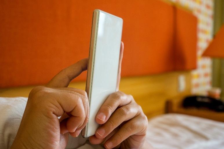 Man browsing sleeping apps in bed