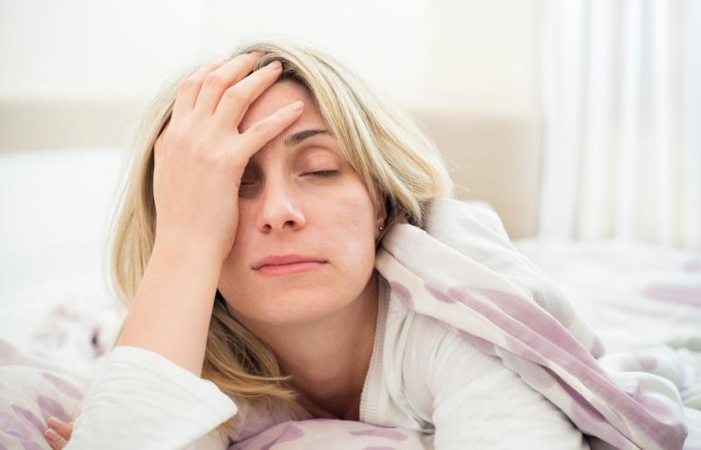 Woman looking tired after sleeping on a memory foam sleeper sofa mattress