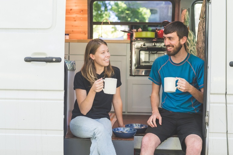 Couple having breakfast and coffee in their trailer