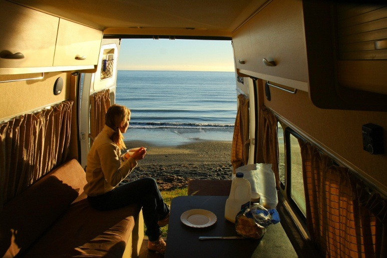 Woman having coffee in RV camped by the seaside