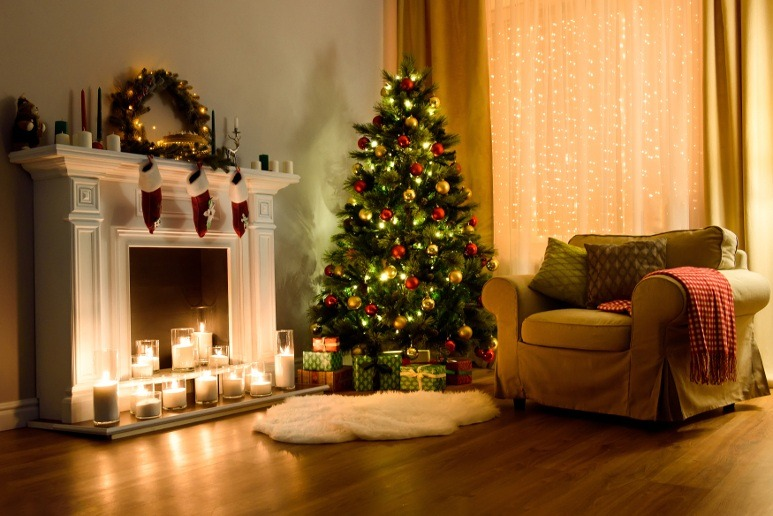 Decorated couch and fireplace next to Christmas Tree