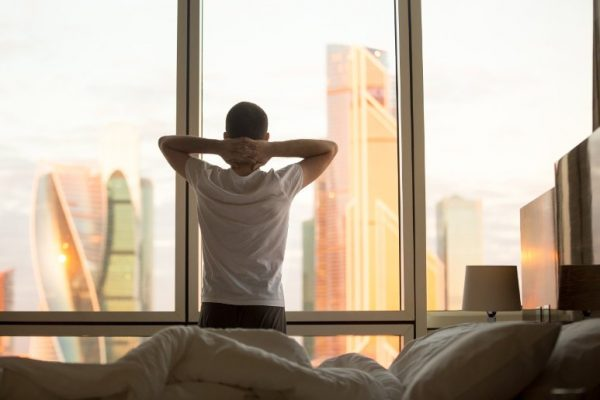 Successful man looking out the window in the morning after a good night's sleep